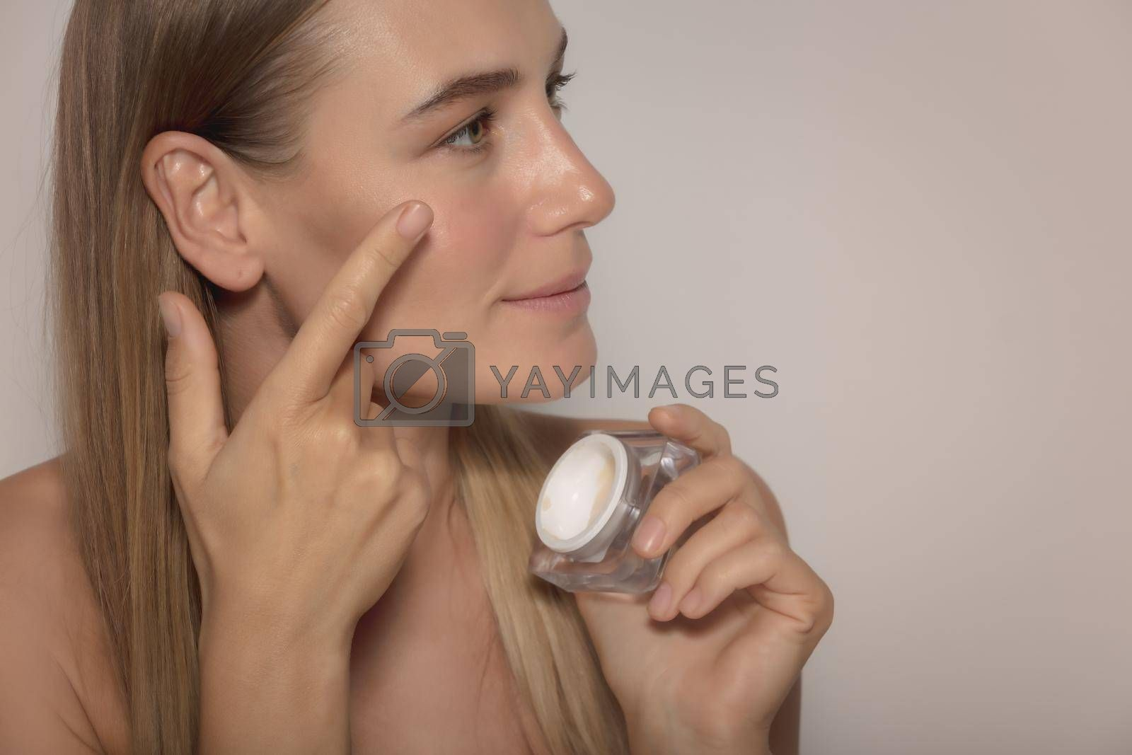Portrait of a Pretty Woman Isolated on Beige Background Applying Face Cream. Young and Fresh Face. Beauty and Skin Care Routine.
