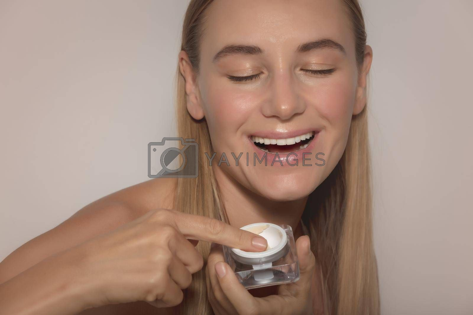 Portrait of a Happy Smiling Woman Uses Facial Cream. Face Isolated on Beige Background. Anti-aging or Anti-wrinkle Product. Beauty and Skin Care Routine.