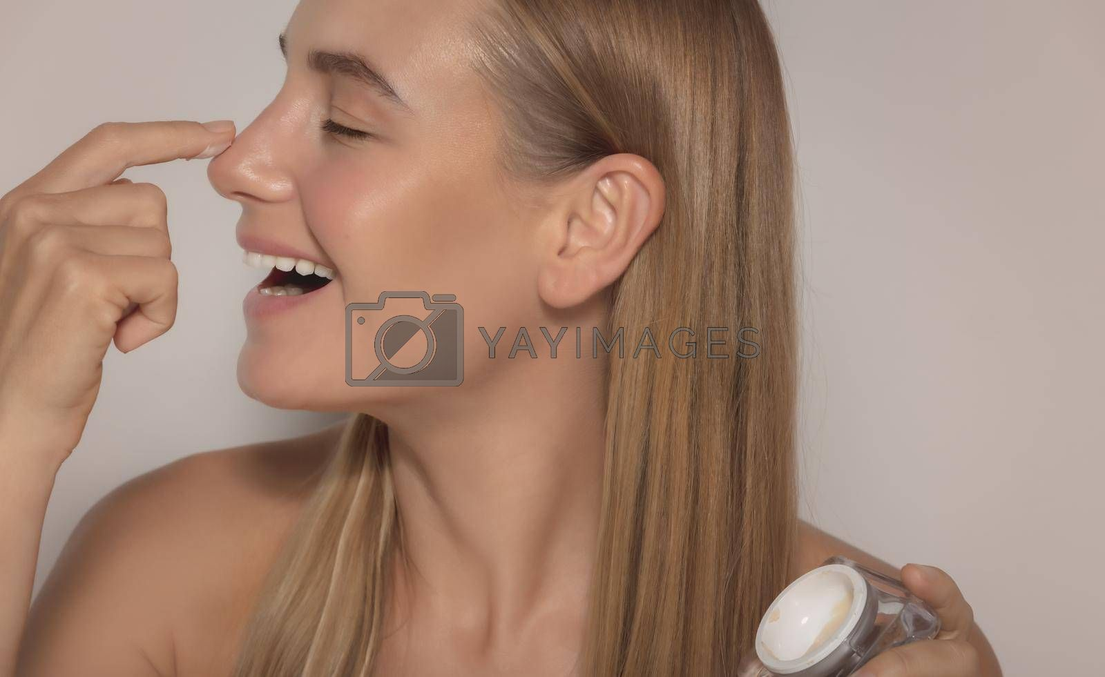 Profile Portrait of a Cute Woman Laughing and with Closed Eyes of Pleasure Trying New Face Cream Isolated on Beige Background. Happiness and Beauty Treatment Concept
