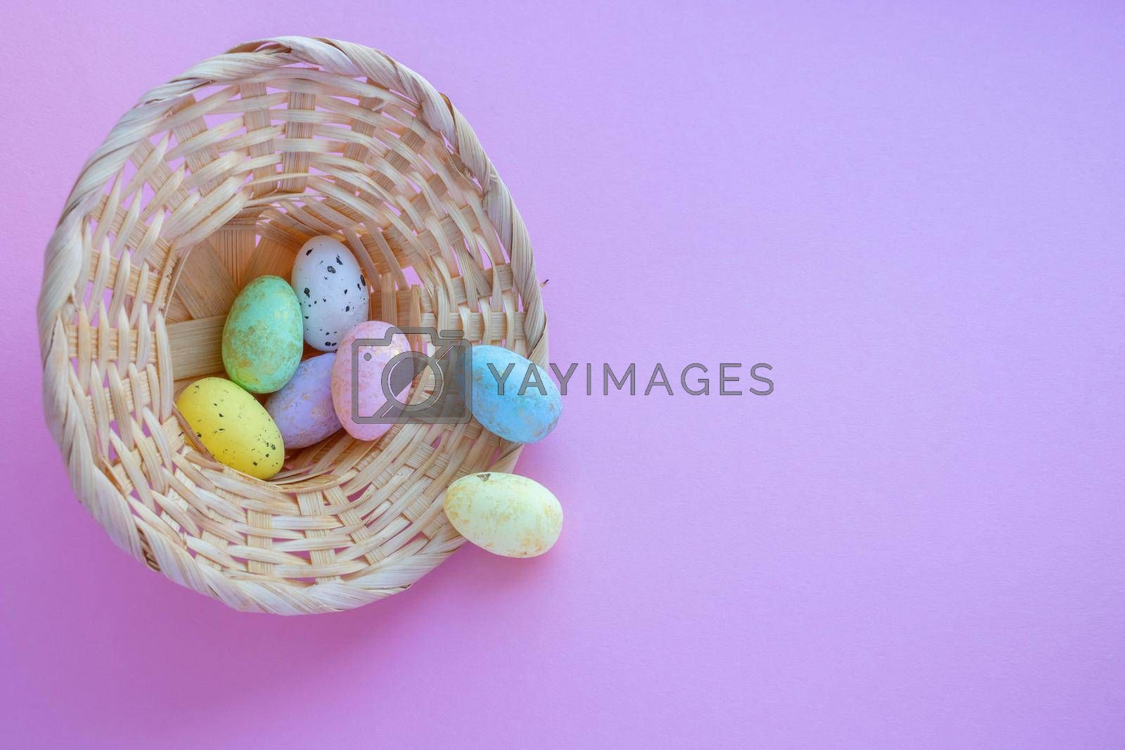 An overturned basket in the shape of a hat with eggs on a pink background. Easter Concept.