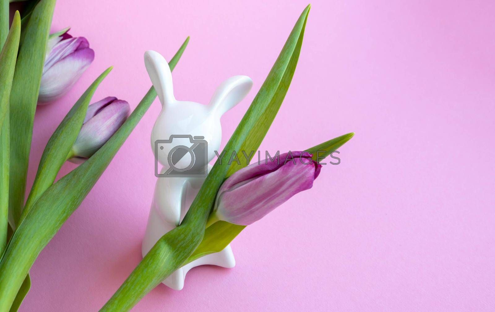 Easter bunny and lilac tulips on pink background, Easter celebration concept.