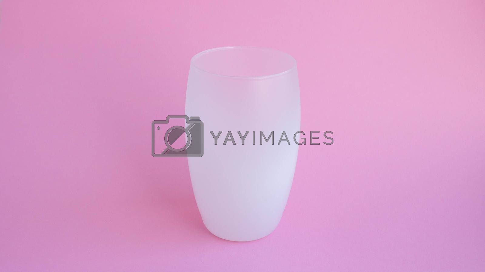 A white frosted drink glass stands on a pink background.