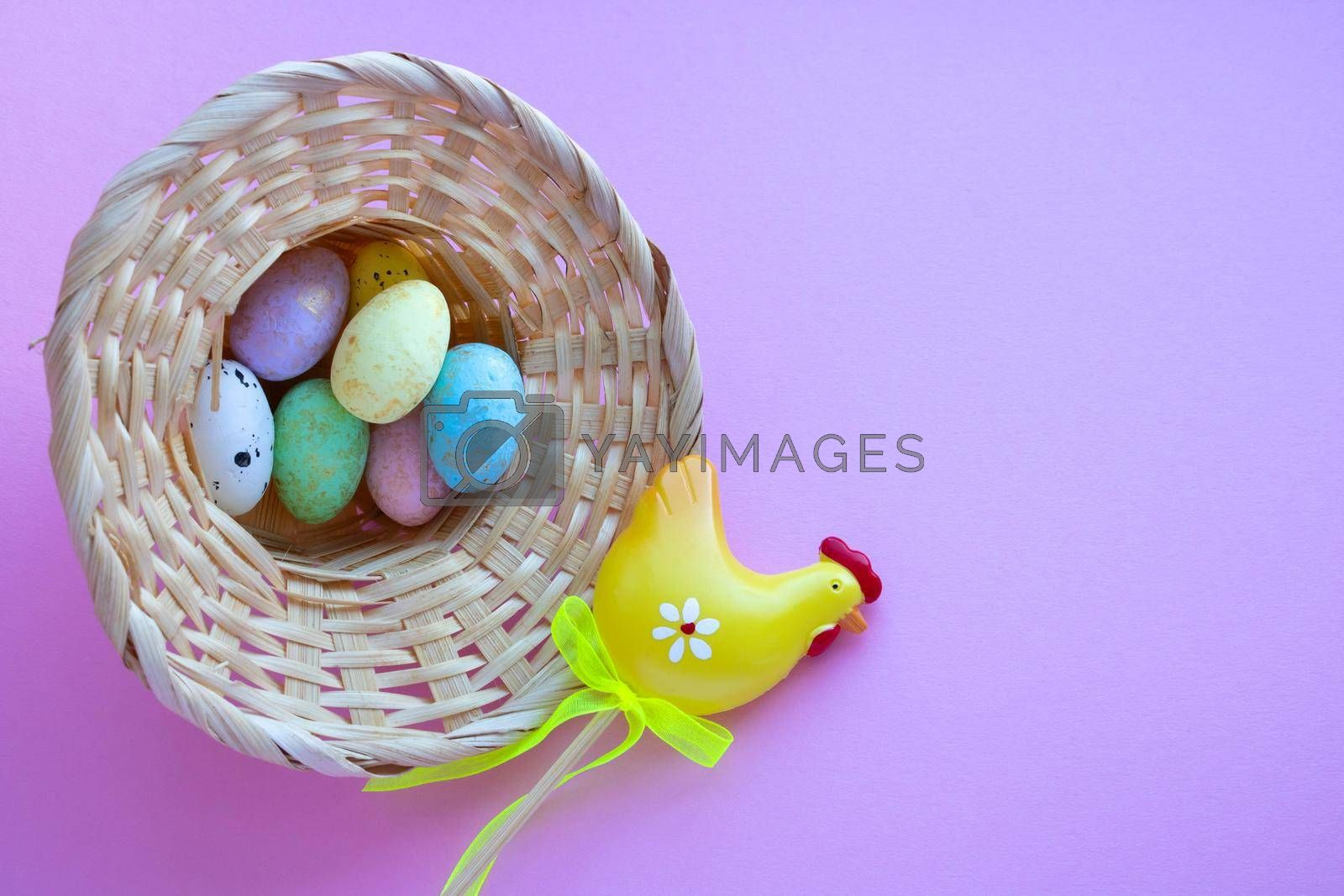 An overturned basket in the shape of a hat with eggs on a pink background. Easter Concept. Space for your text.