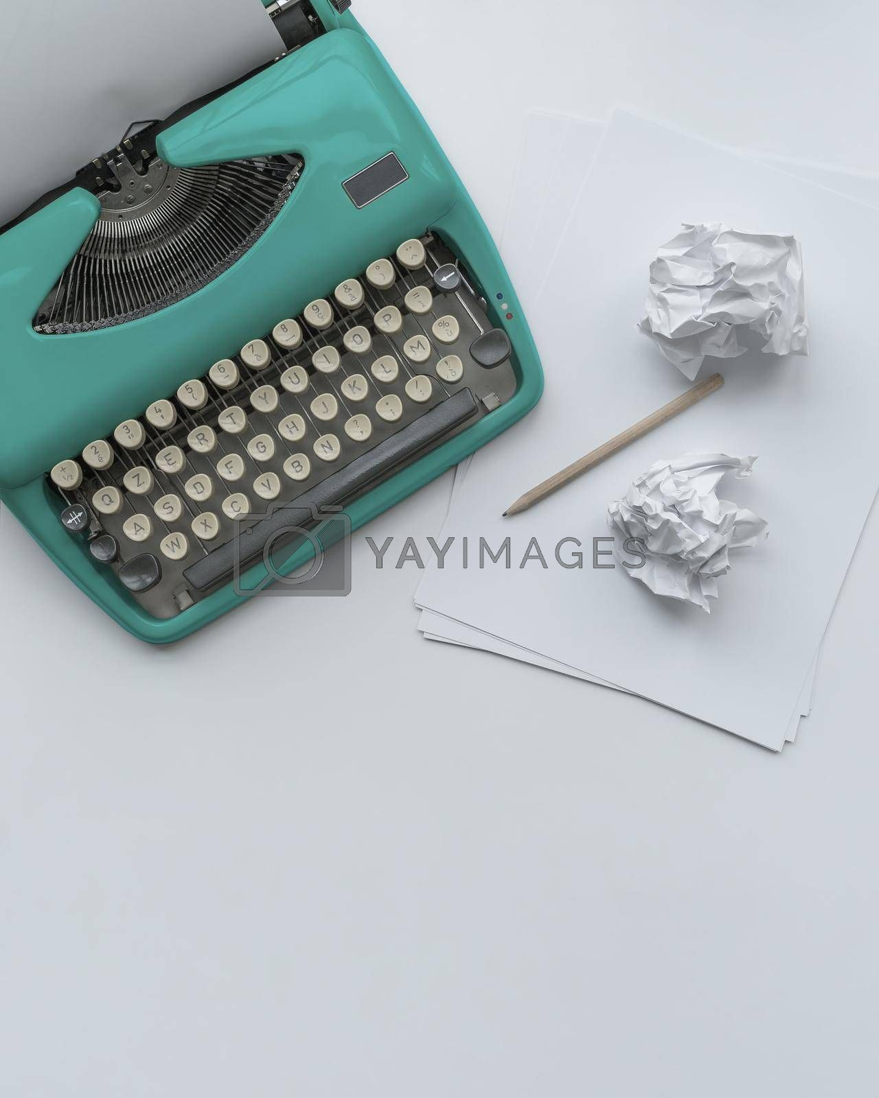 Royalty free image of A vintage typewriter with paper sheets, stencil and paper balls.  by maramade