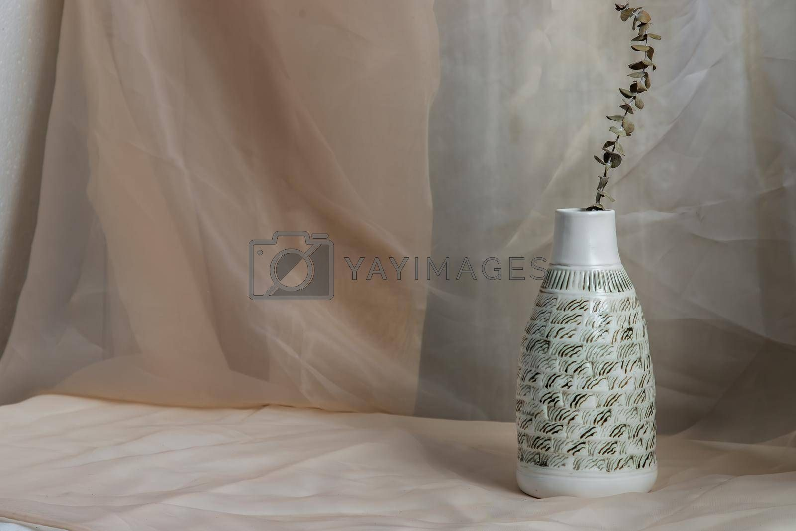 Dried flowers in White ceramic vase bottle shape on Blush textured table cloth. Home decor, Copy space, Selective focus.