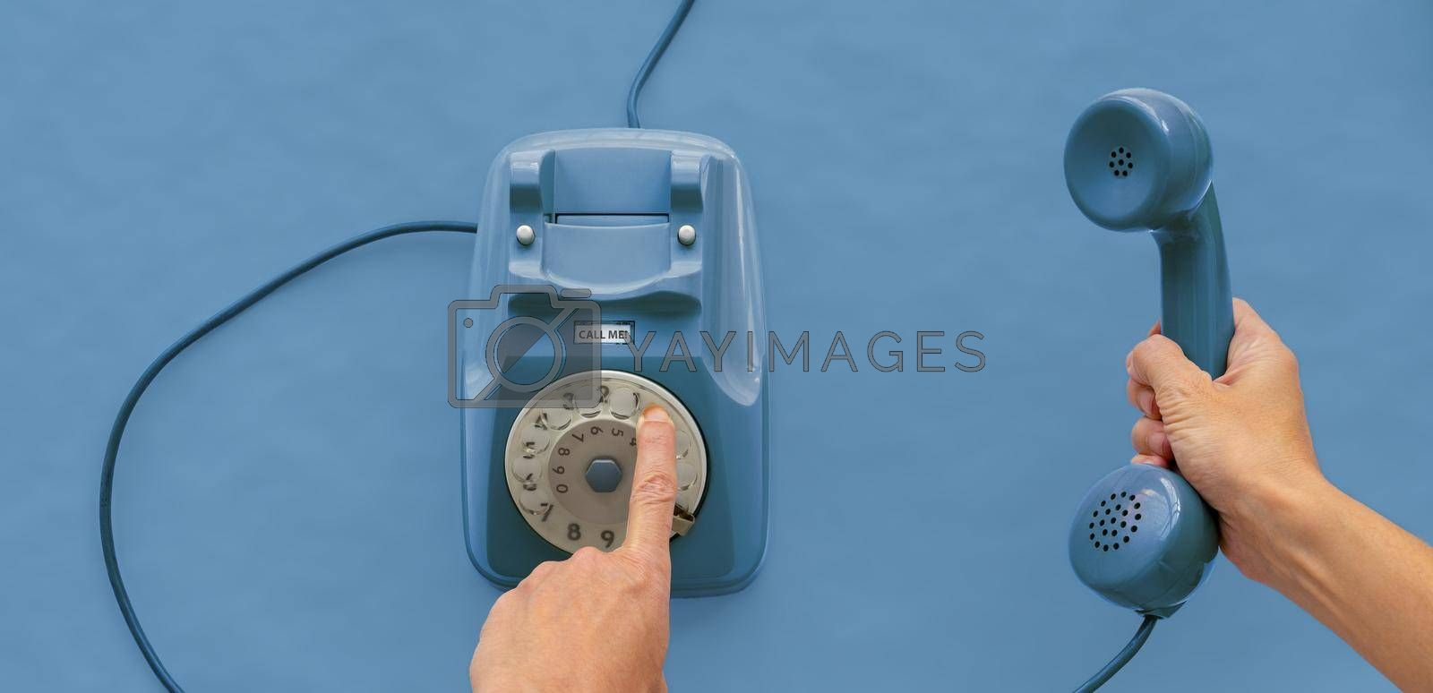 Royalty free image of A vintage dial telephone handset with one hand and background.  by maramade