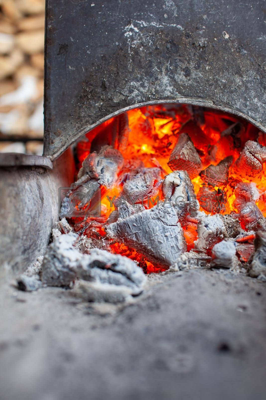 Burning coals in a metal grill for frying meat and vegetables. Cooking on a campfire.