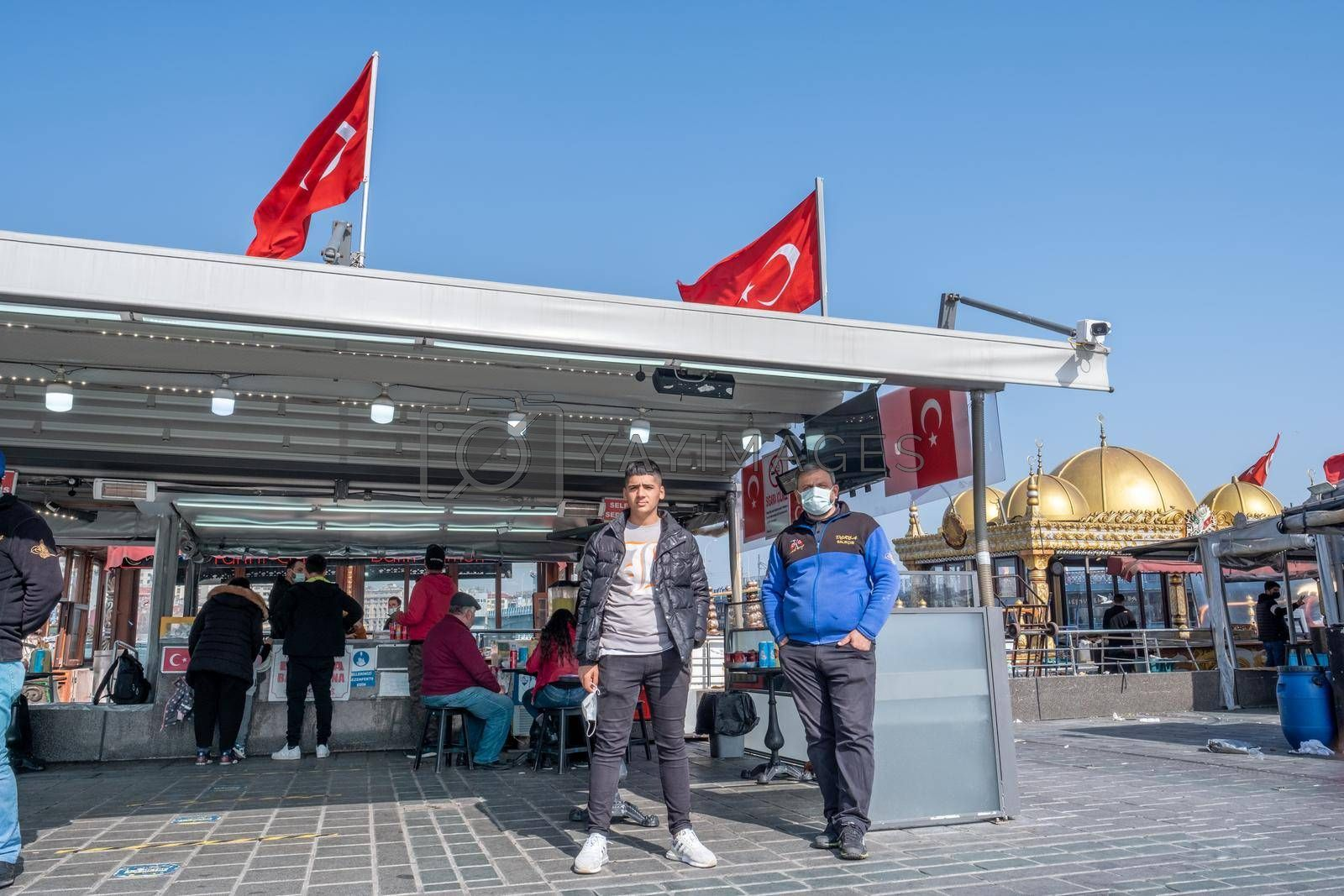 father and son fishermen stand in front of their boat restaurant in Turkey