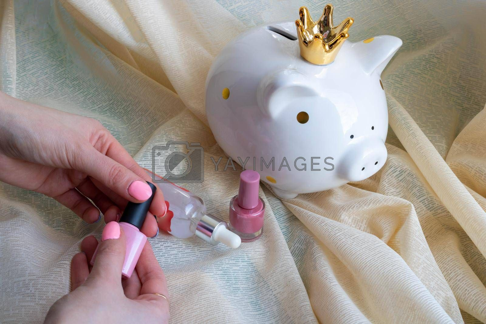 White piggy bank-piggy and female hands with pink nail design. Pink shiny nail polish manicure. Women's hands on a background of beige tulle.