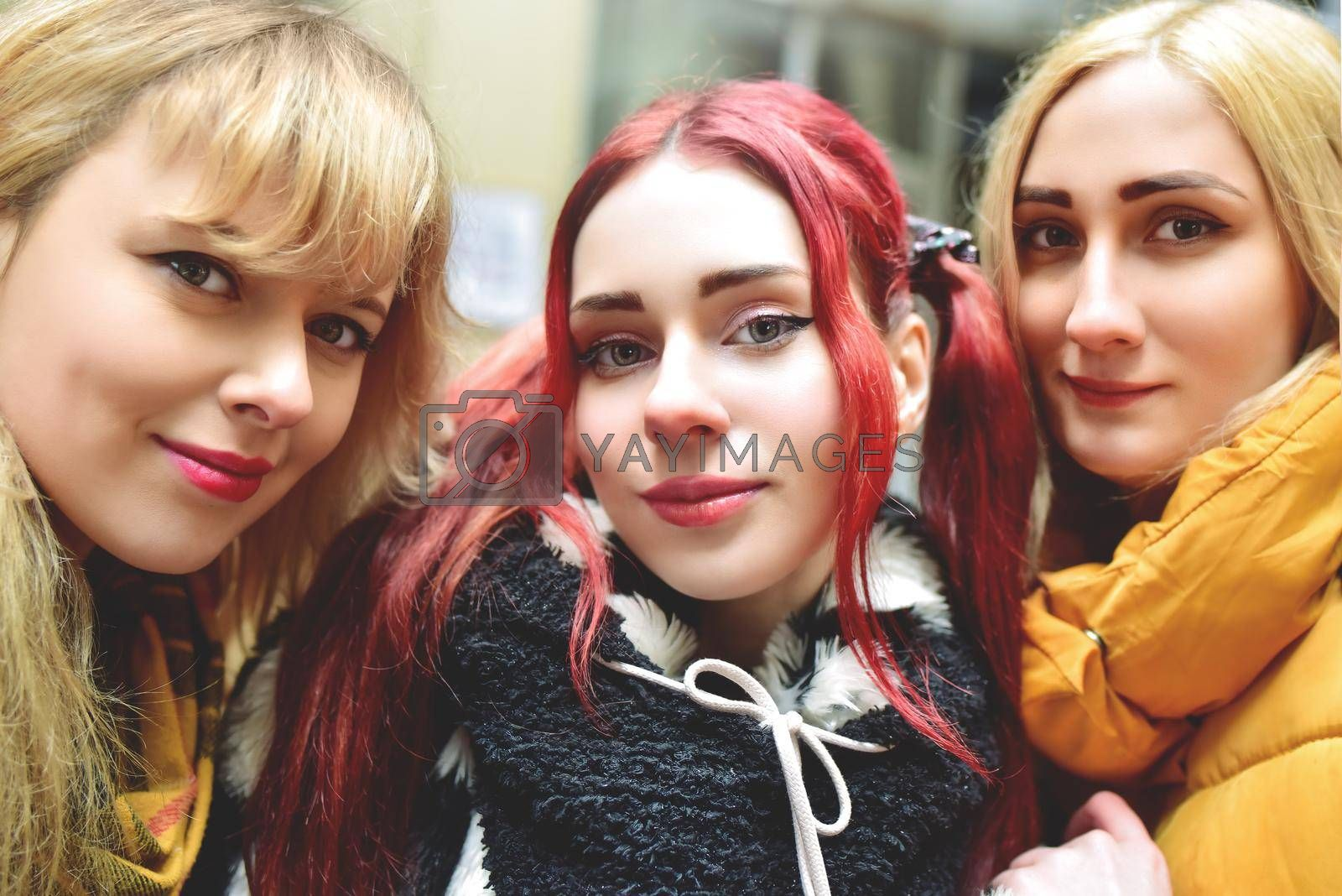 Three beautiful girlfriends in good spirits take a selfie in town. The concept of friendship