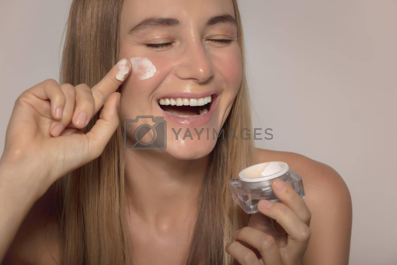 Portrait of a Nice Smiling Girl Laughing and Applying Facial Moisturizer Cream Isolated on Beige Background. Natural Cosmetics. Healthy Lifestyle. Beauty and Skin Care.