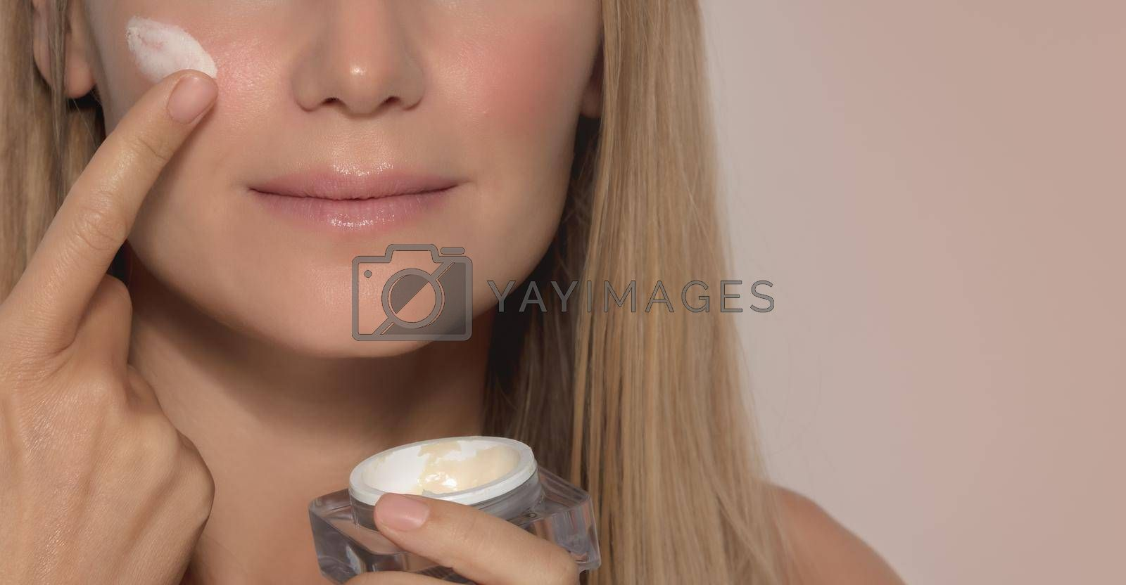 Portrait of a Nice Girl Applying Facial Moisturizer Cream Isolated on Beige Background. Face Part. Natural Cosmetics. Healthy Lifestyle. Beauty and Happiness Concept.