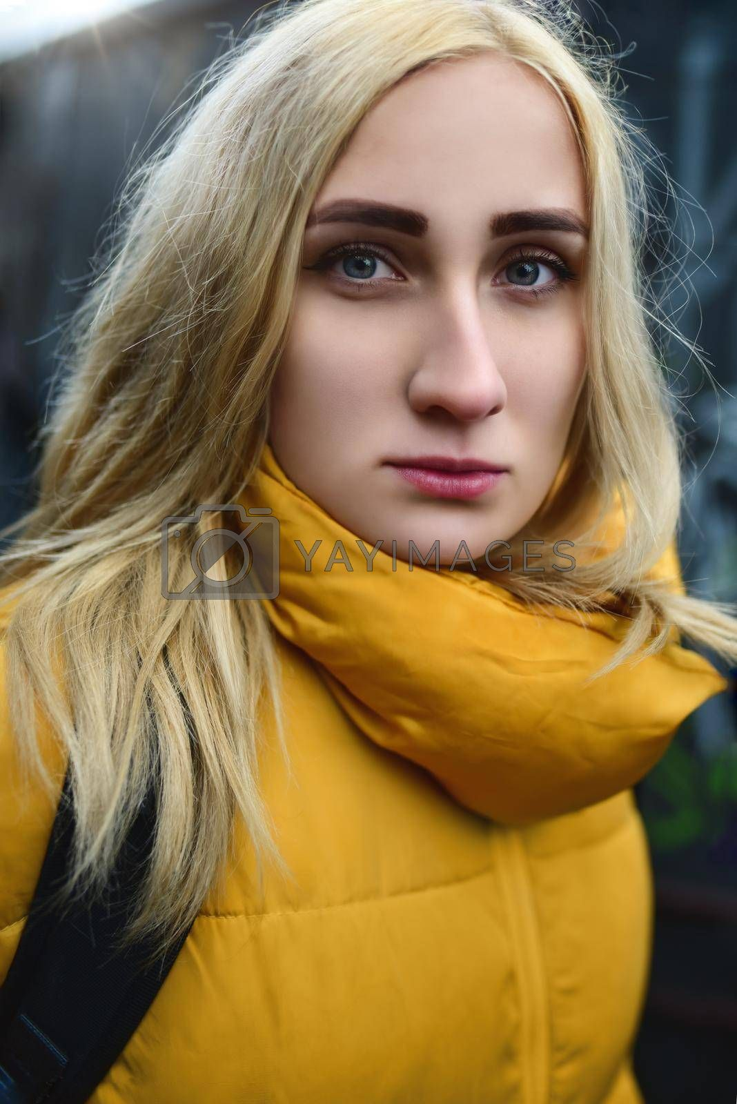 Close up portrait of blonde hipster teen girl making selfie, She is wearing yellow jacket and backpack, walking outdoors throught underground passage and making selfie