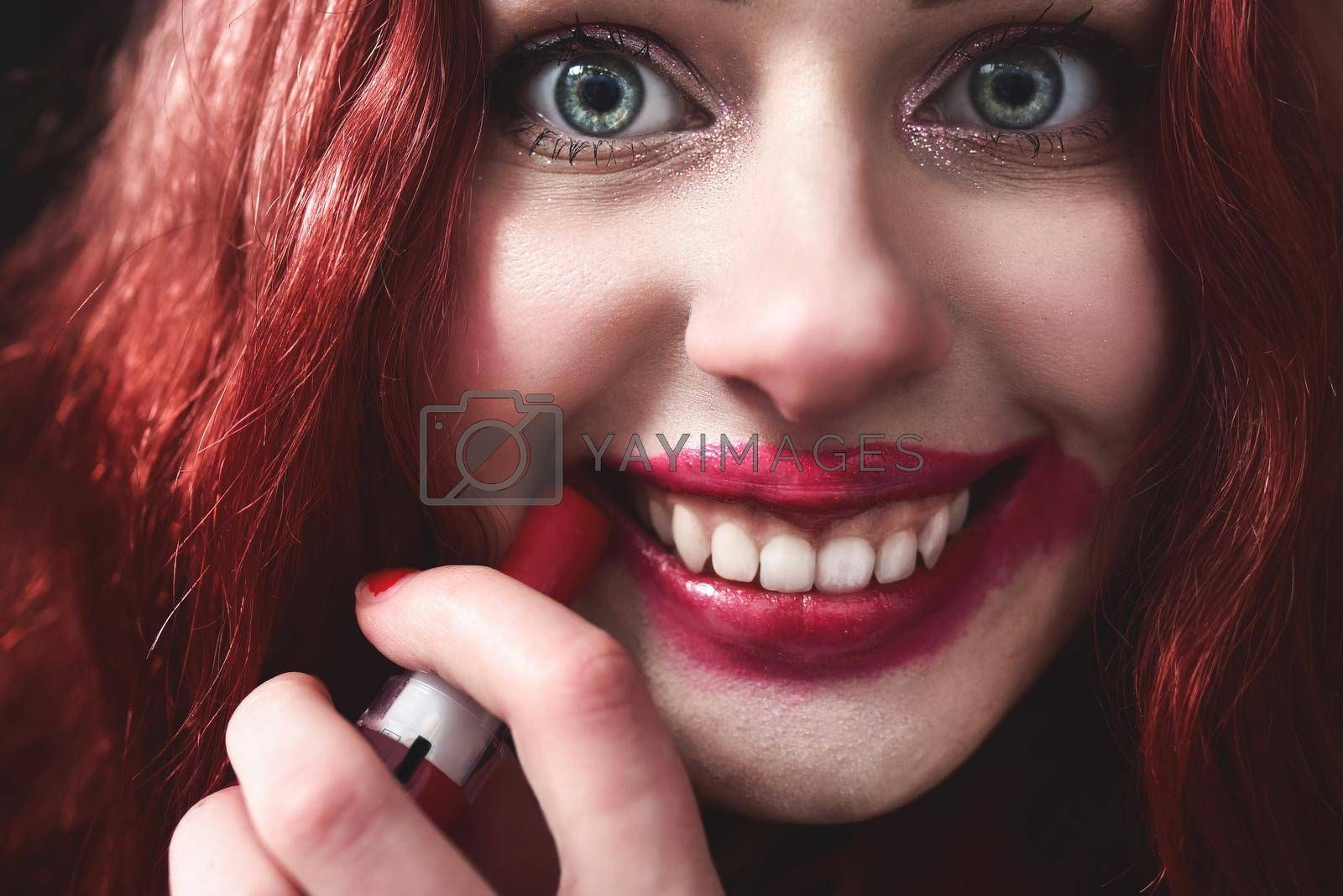 Portrait of crazy-looking teen girl with red hair she is smearing red lipstick on her face, horror concept. halloween time. Fear and nightmare. close view