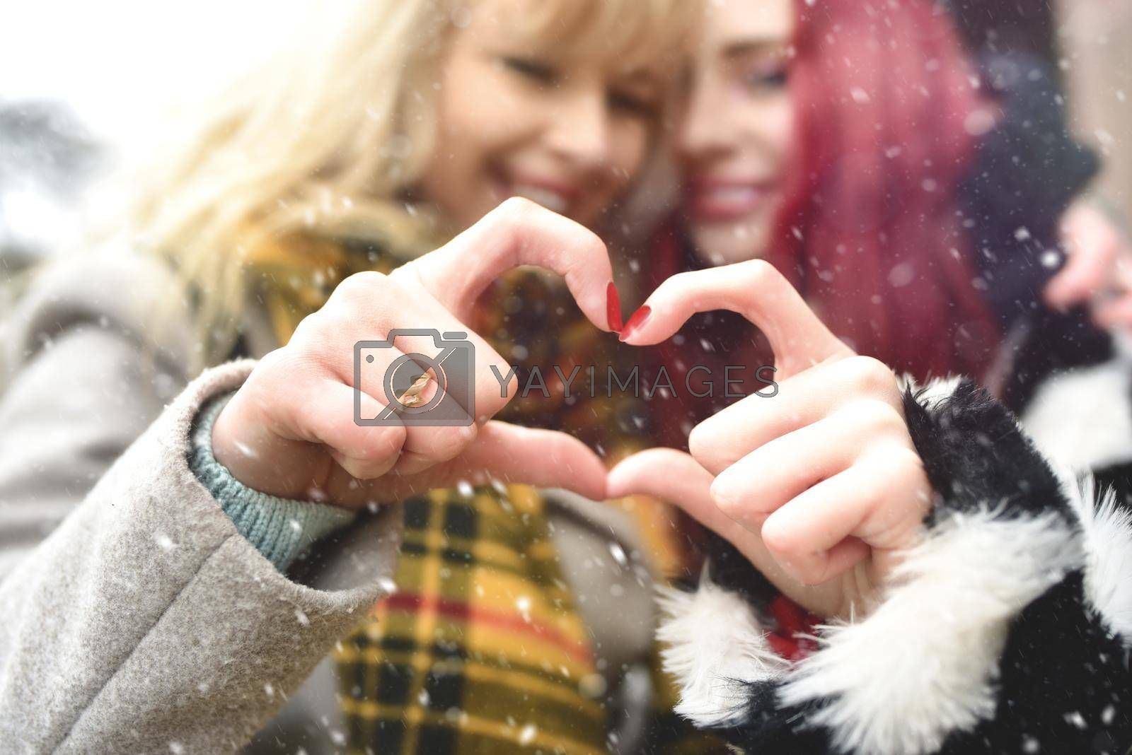 Lesbian couple making heart with hands, open relationship in love. love concept. friendship concept. snowy effect