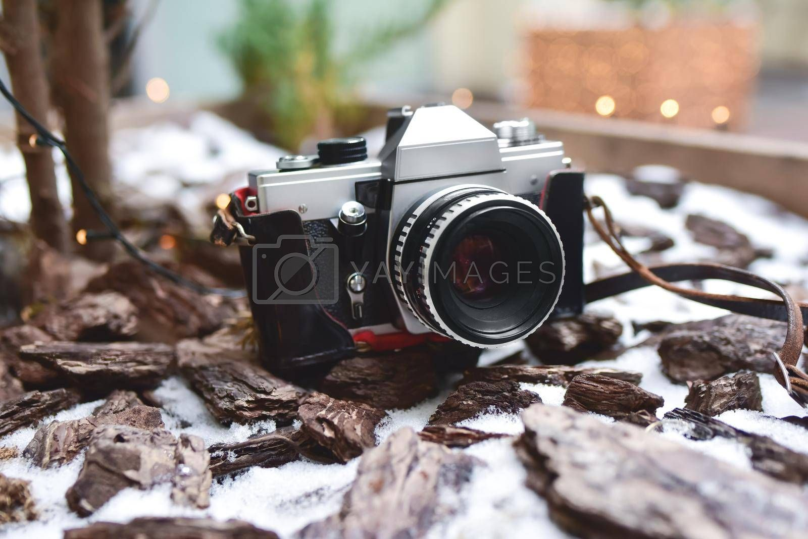 A single, old, retro photo camera it stay on the snowy ground.