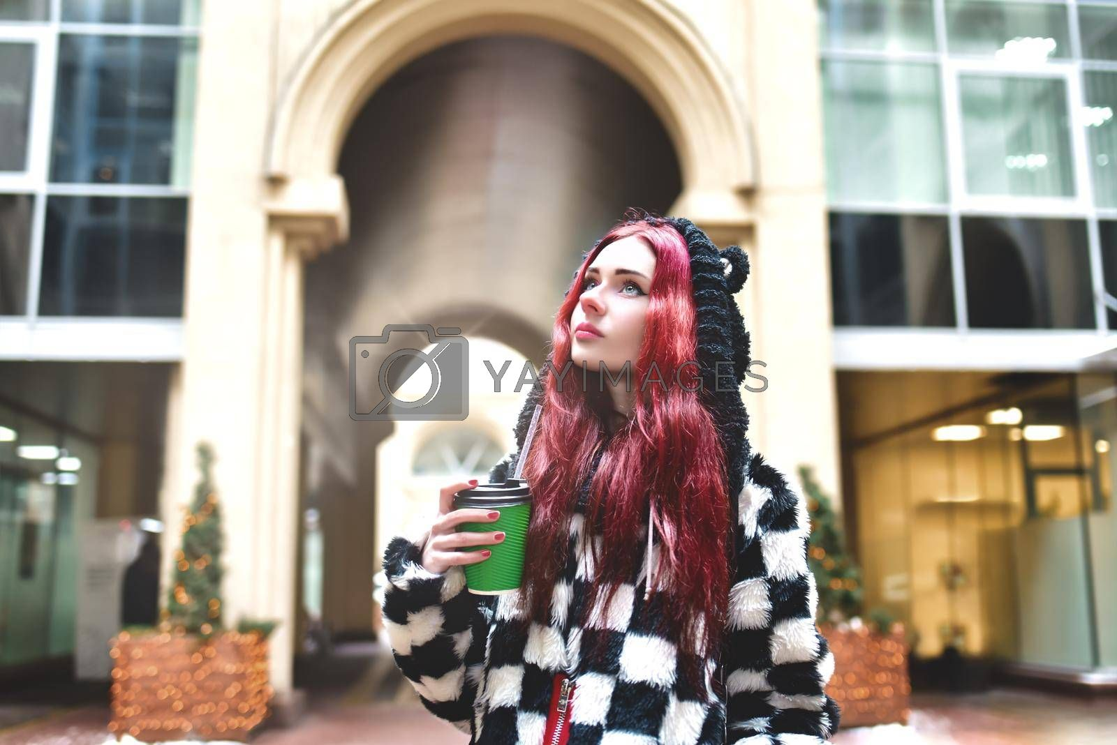Near portrait of a teen girl with red hair in warm clothes standing outside on a cold day with a cup of coffee in her hands and looks into the camera. Cute girl walking with coffee in her hands and playing with own hair.