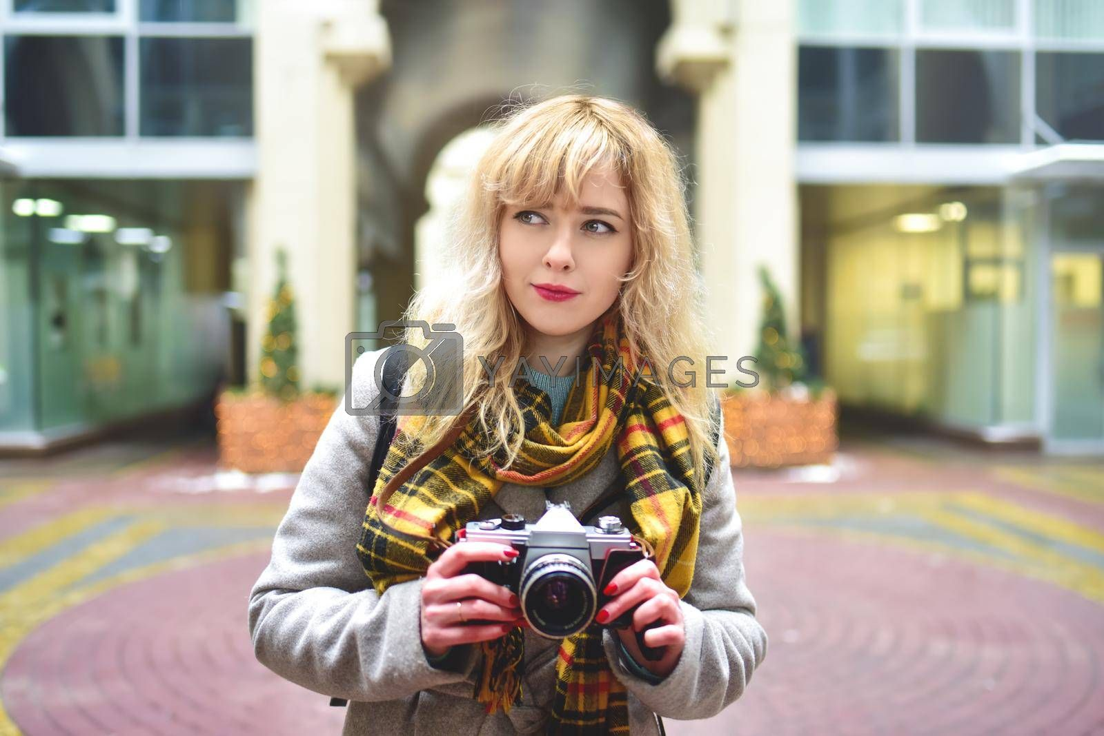 Blonde pretty photographer woman with retro camera in her hands while taking pictures at urban old architecture. Discover new places.