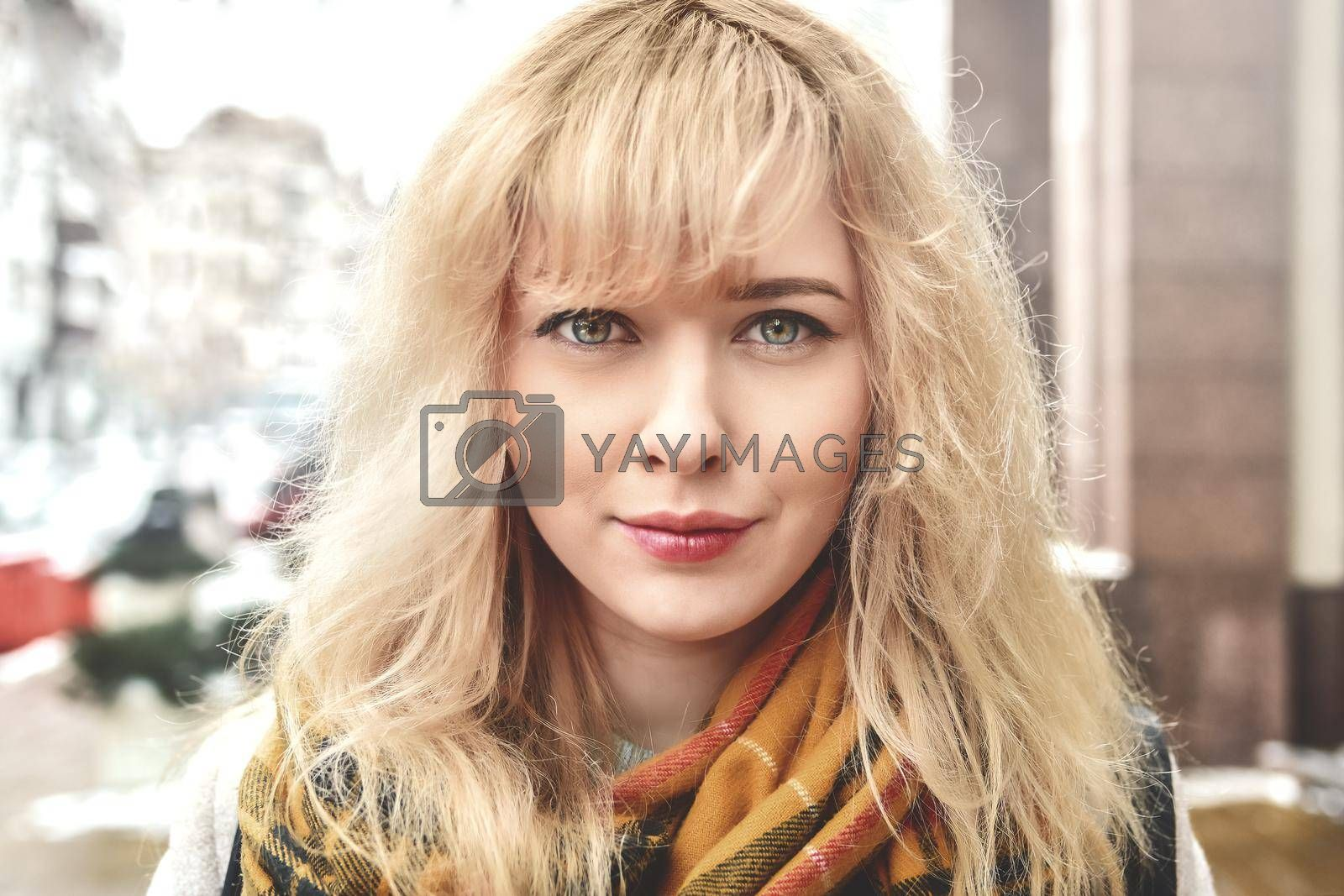 Urban portrait of a beautiful smiling Caucasian girl with blond curly hair looking at the camera
