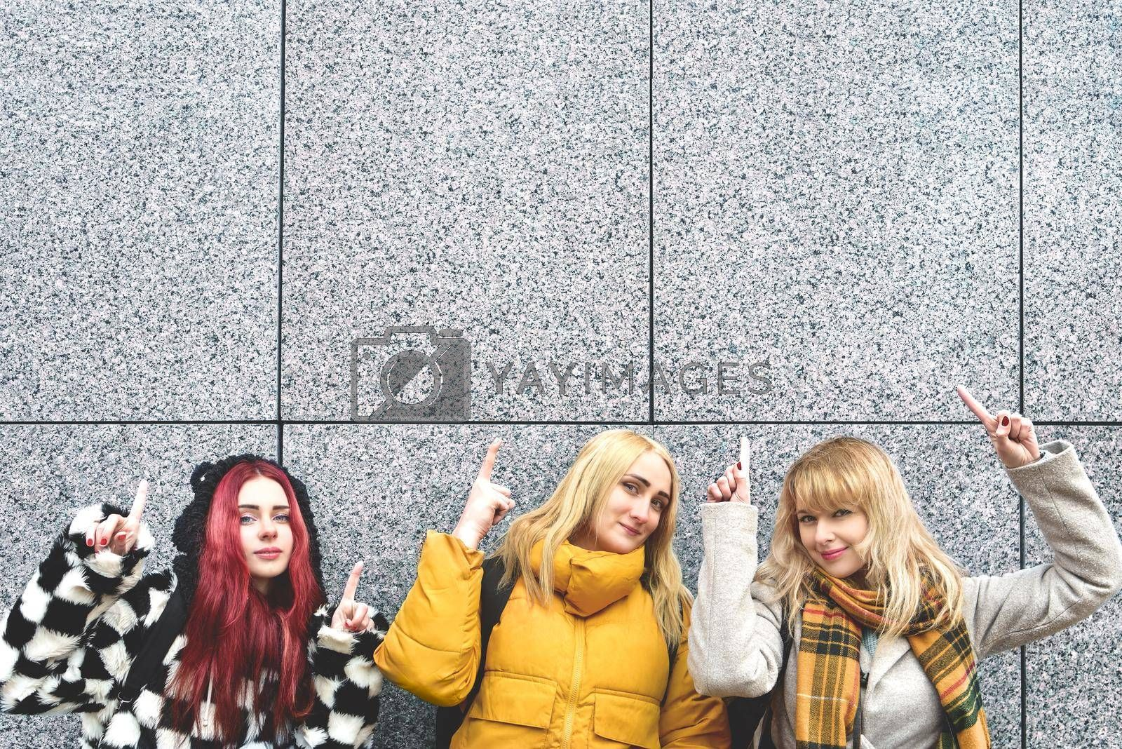 Cheerful girls at the street, show a big sale, or nice offer. Advertise concept. People, travel and tourism - women on city street show with their fingers something over gray wall background