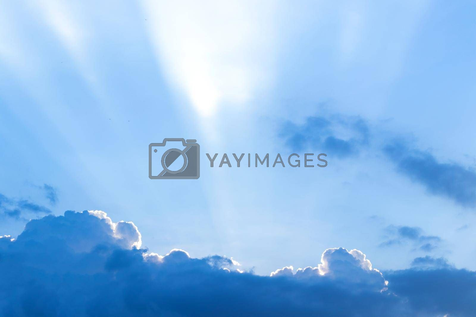 The sun ray behind the clouds in the blue sky.