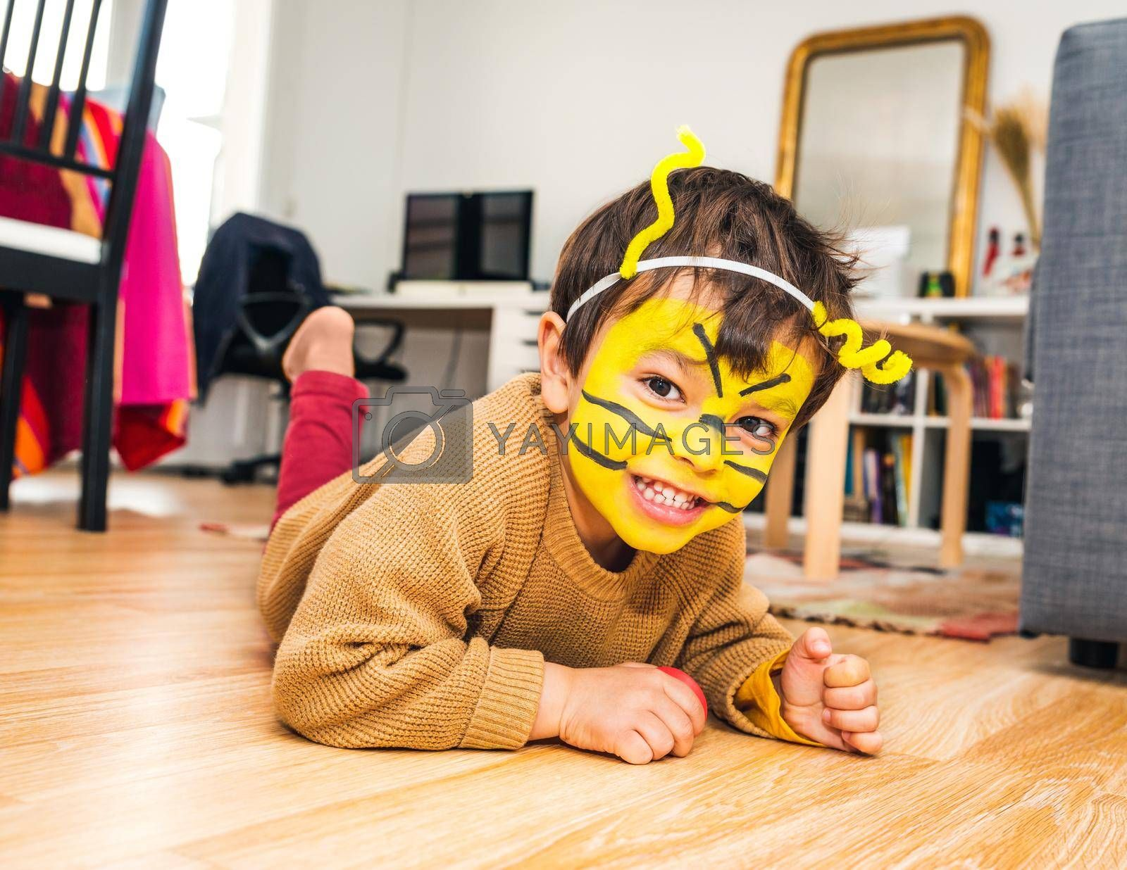 Little boy with bee face paint and playing at home