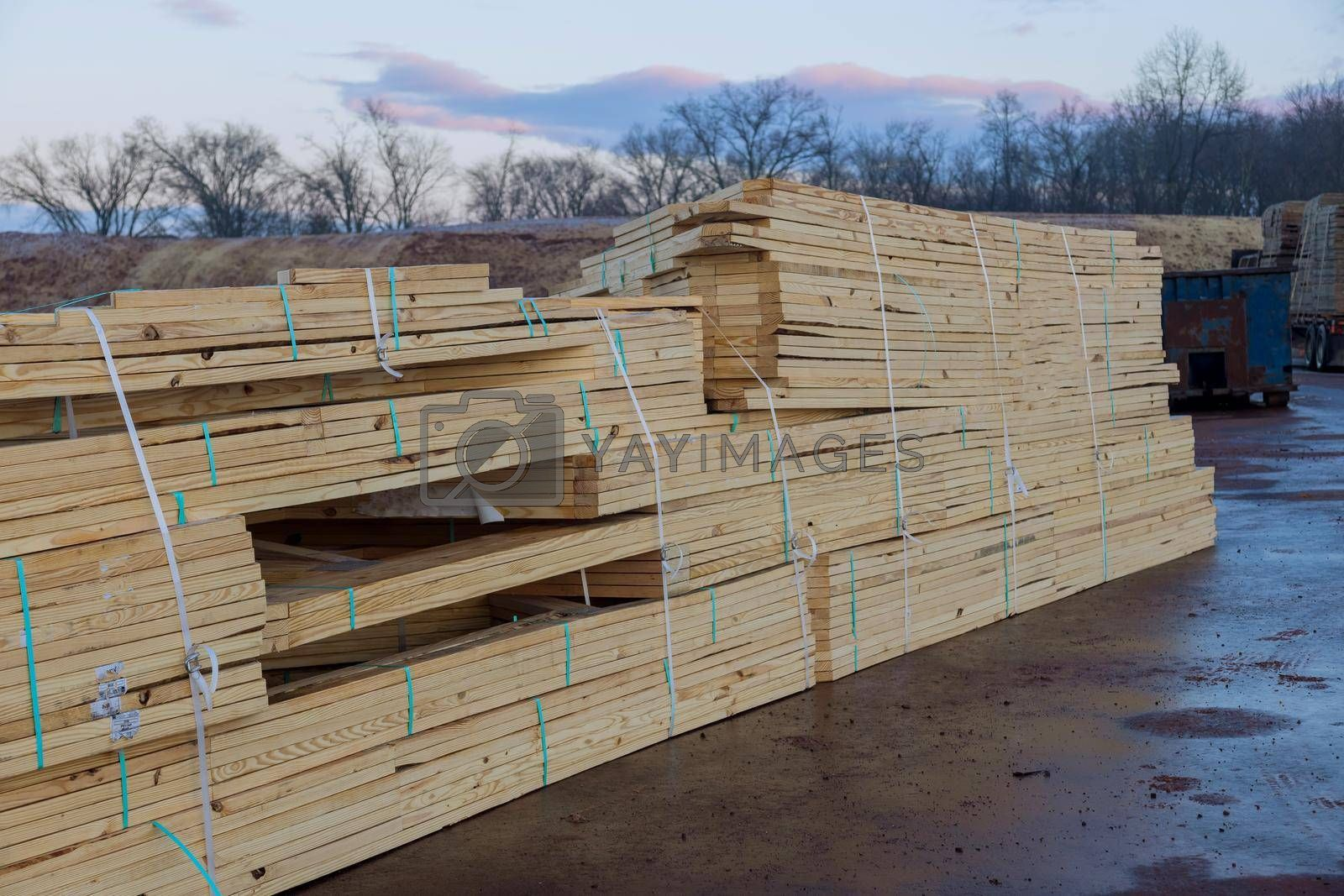 Wood stacked on house building materials from at a construction site.