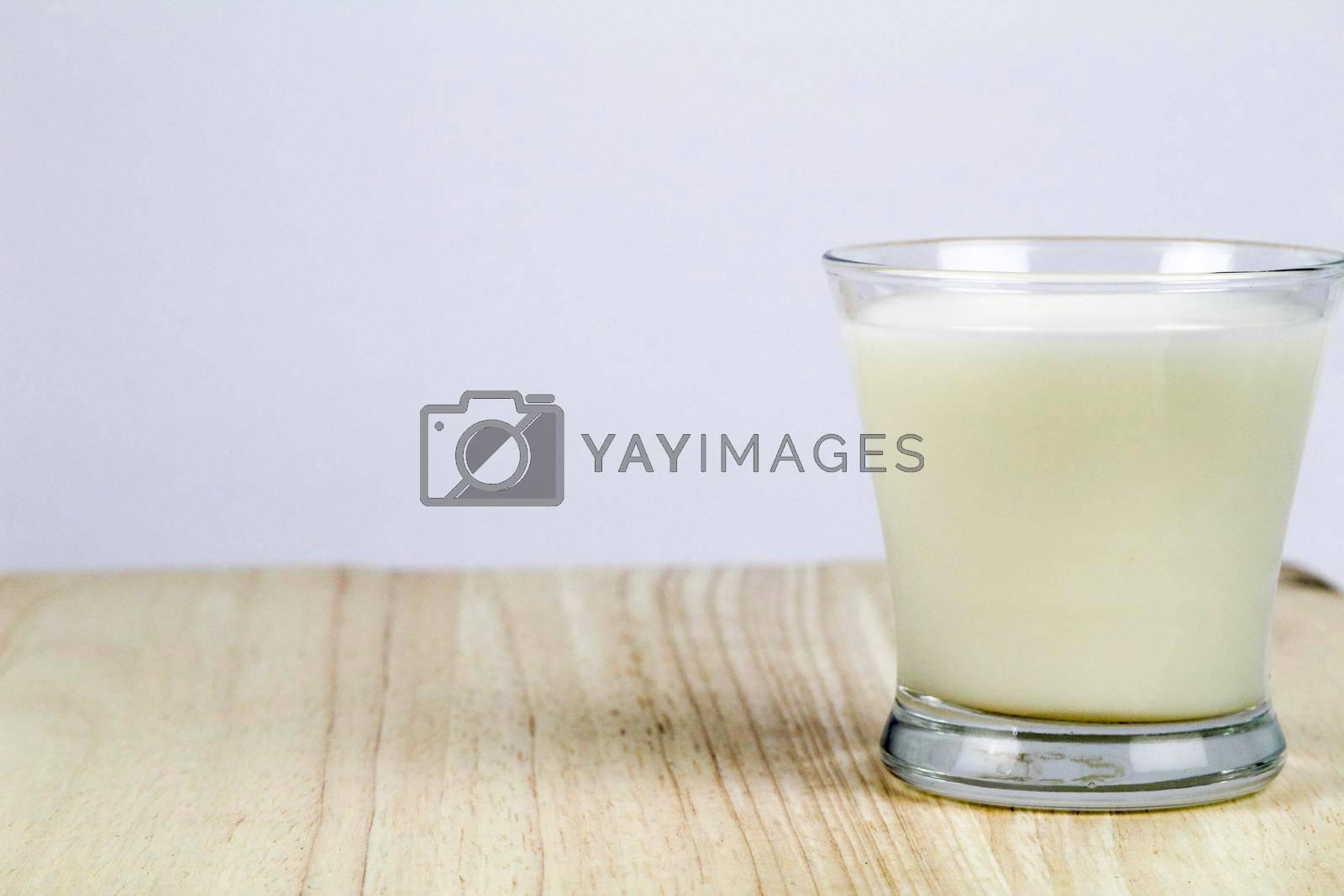 Little glass of fresh milk on wooden table
