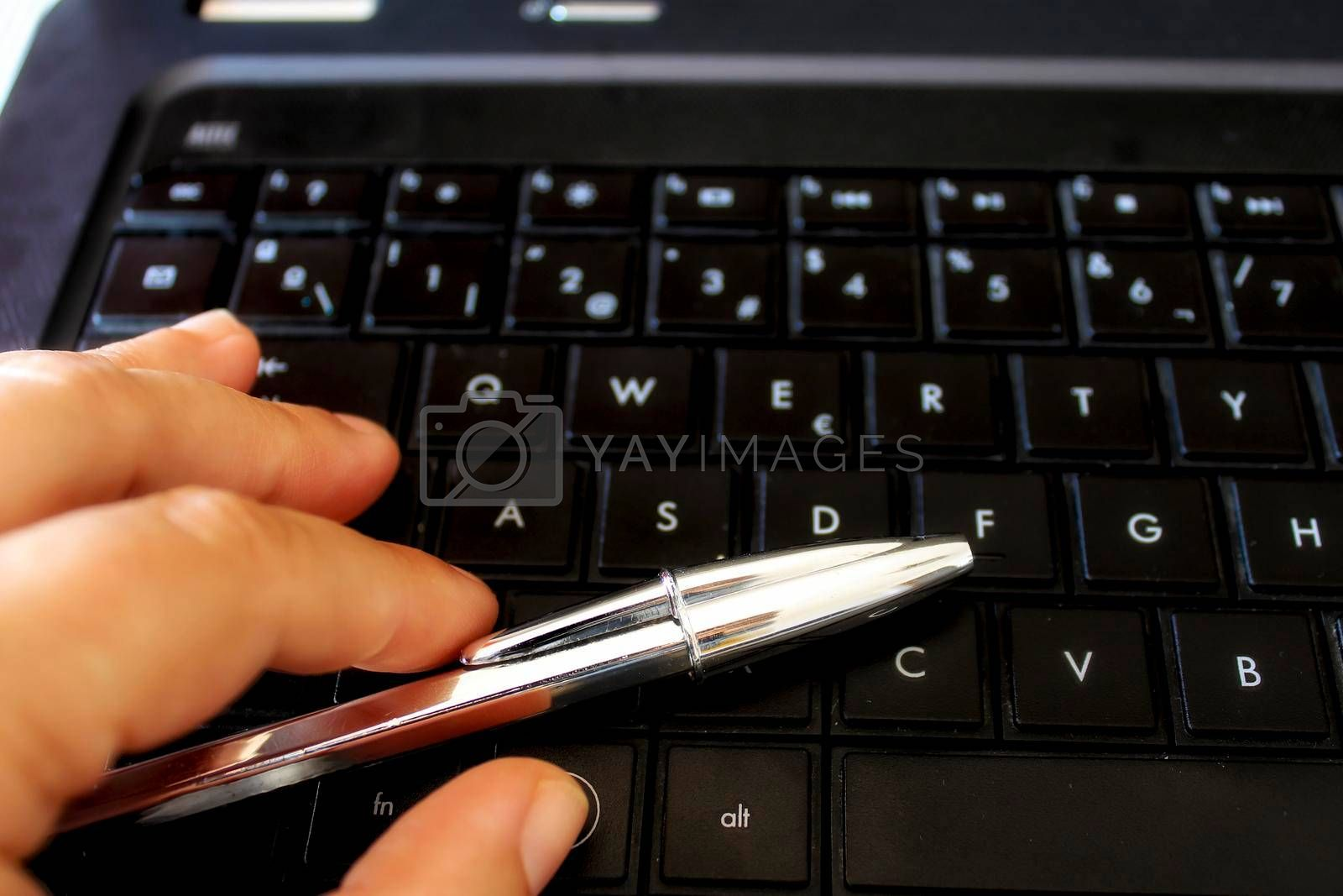 Hand with pen on black keyboard laptop while working