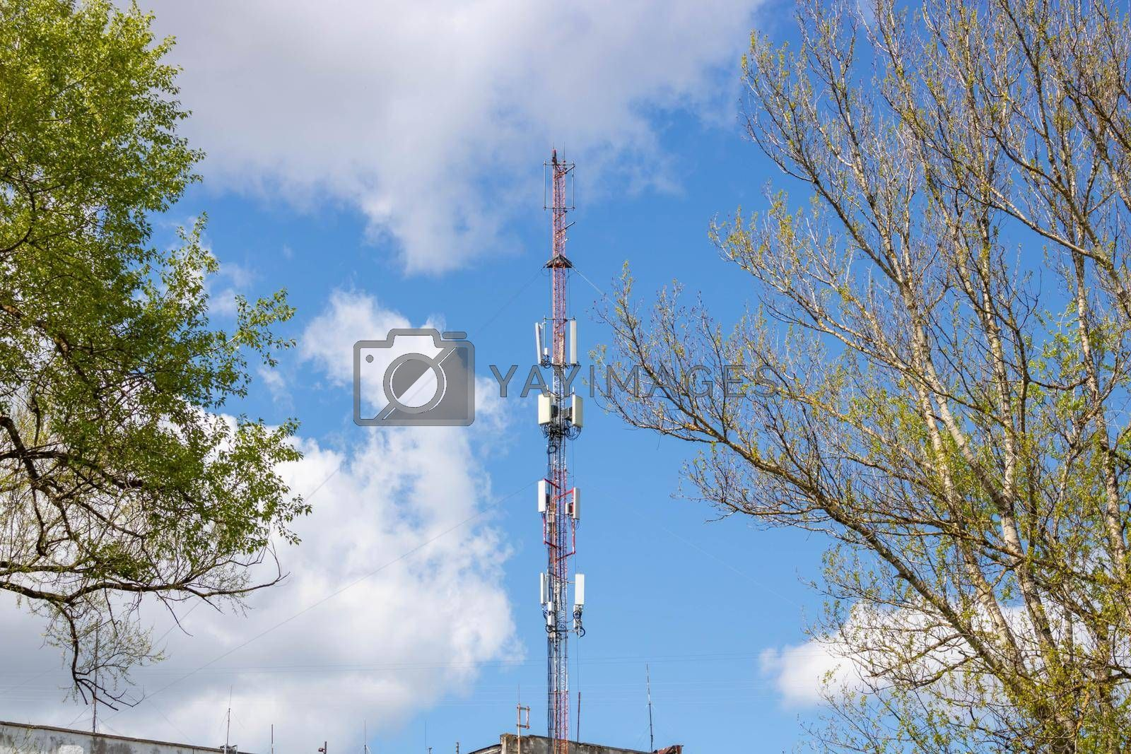 Cellular network or mobile antenna in the roof of a building, on cloudy sky.