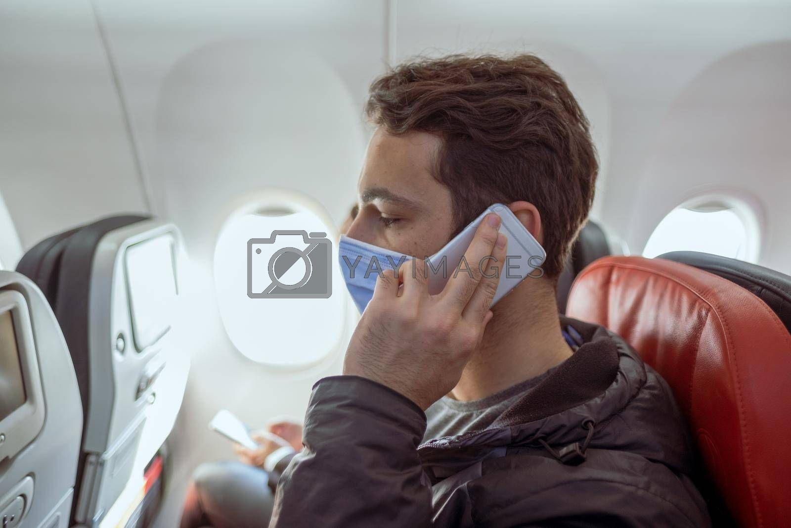 young man with gray coat talking to smart phone in airplane in quarantine times