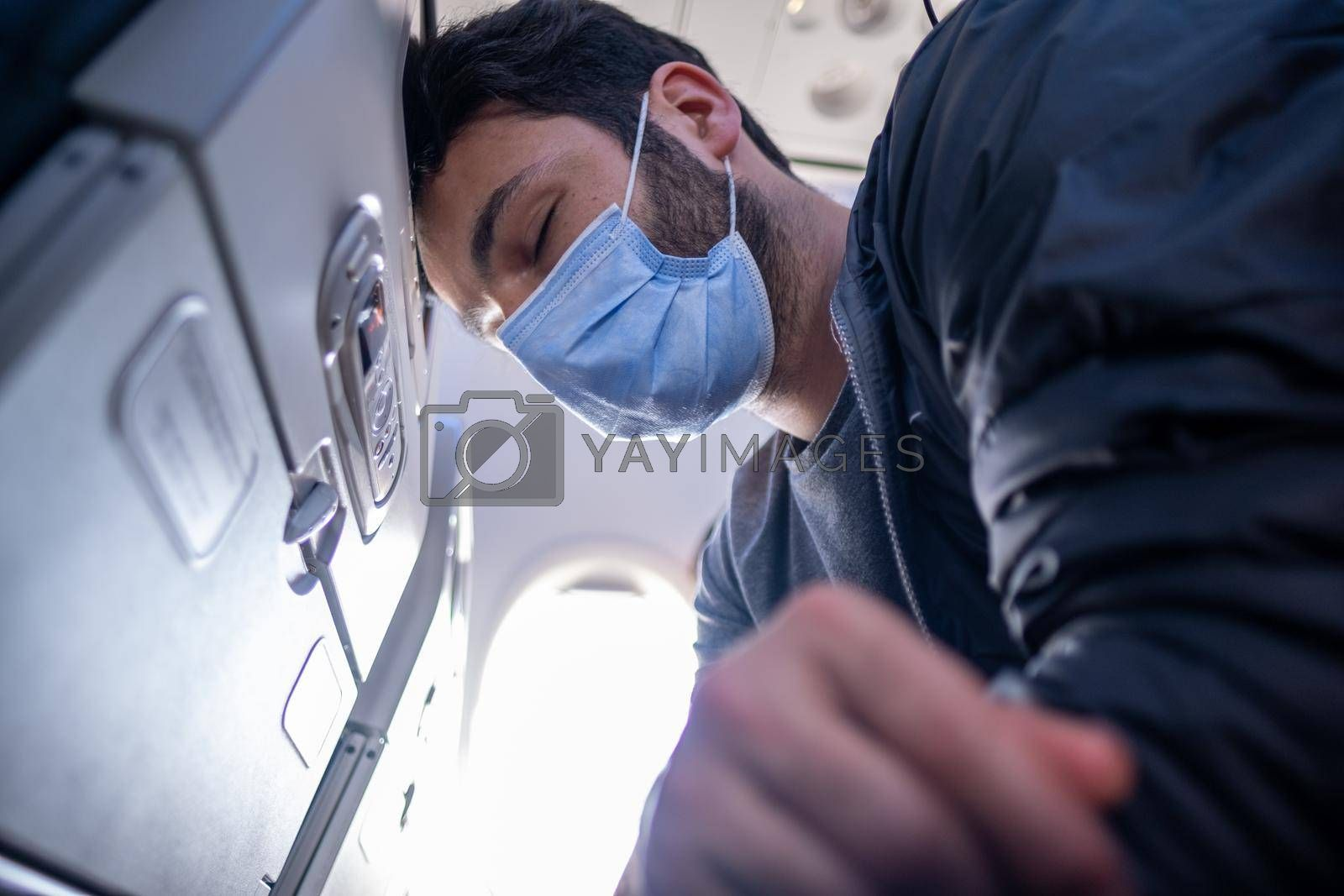 young man with mask having headache because of air trip while sitting on plane seat and sun shines behind in quarantine days