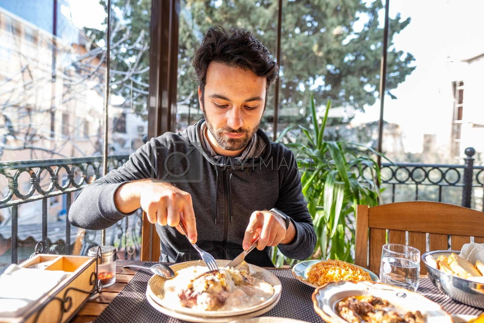 happy male person eats his meal on plate in a restaurant