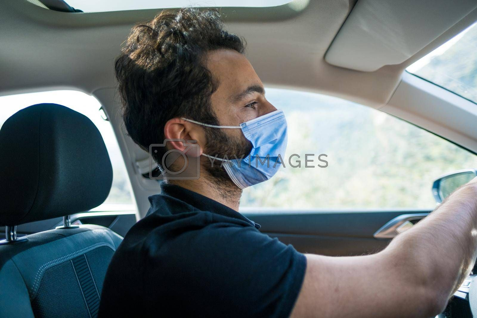 a male person holding steering wheel and driving in a focused way