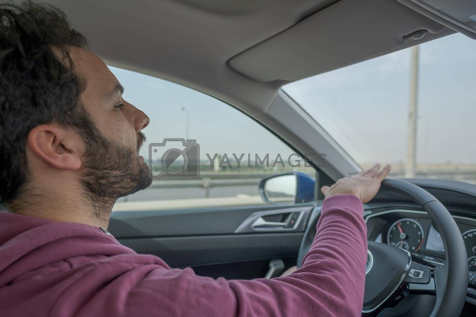 handsome young male person driving a car in a fast speed in daylight