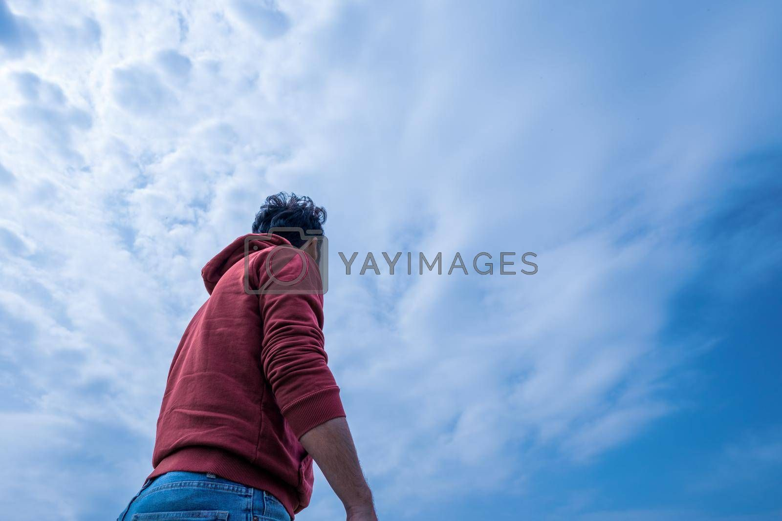 medium shot of a male person from low angle depicting him standing in a bright air
