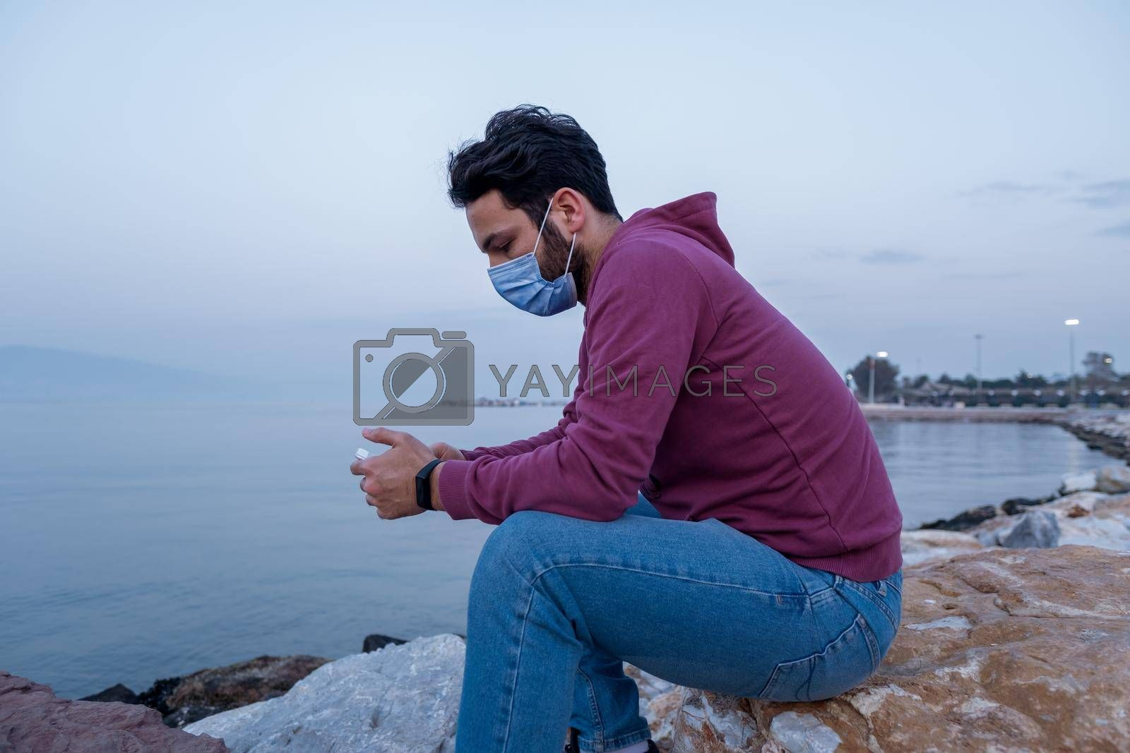 alone one male person sitting ashore and looking at phone screen and checking internet