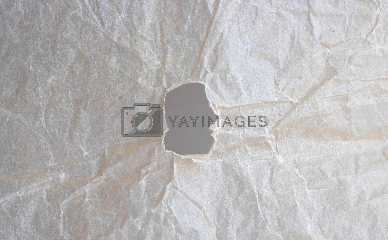 Abstract background of beige crumpled paper with a hole.