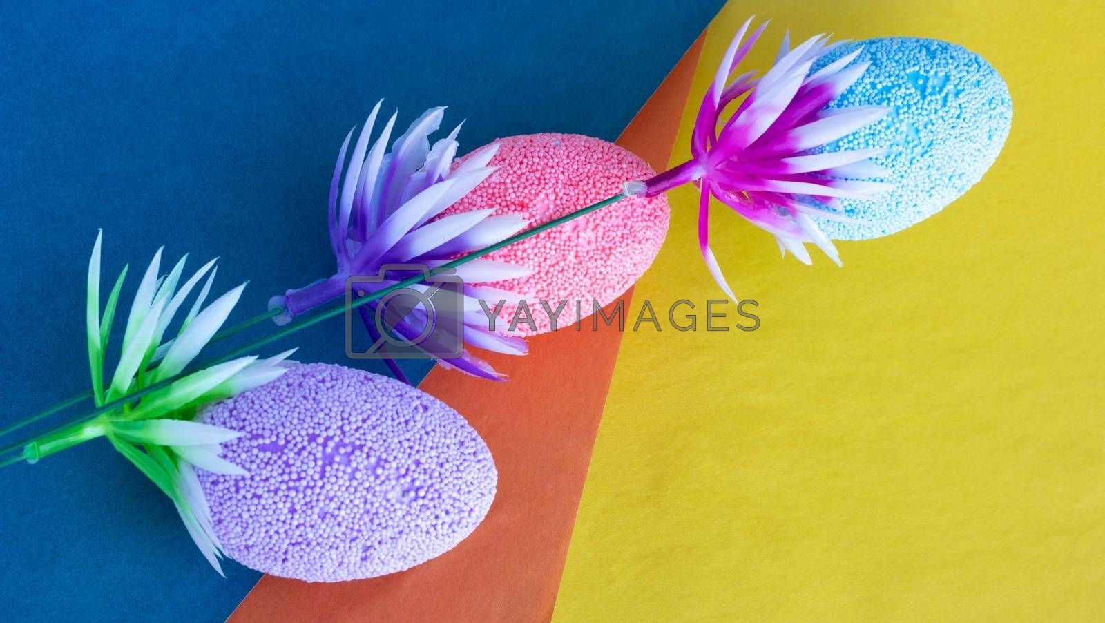 A twig with colorful Easter eggs lies on colored paper.Easter Concept.