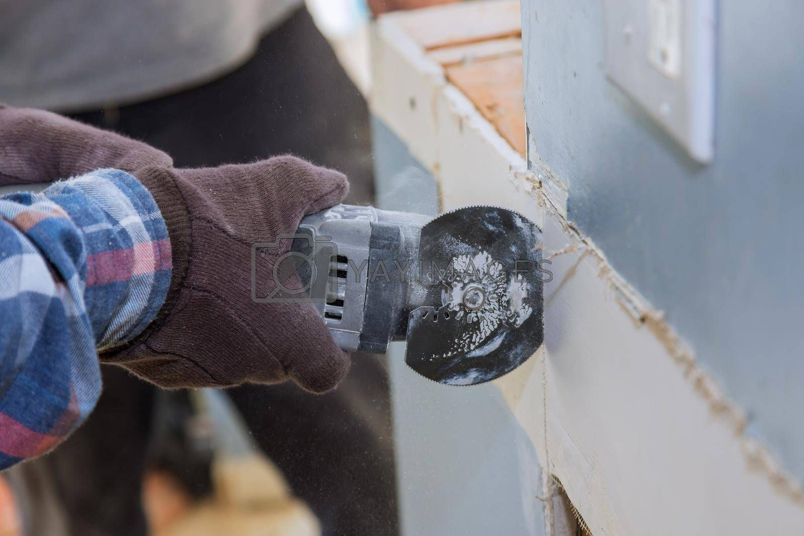 Maintenance repair works home remodel of replacement damaged drywall on man is cutting gypsum board with utility hand electric power tools