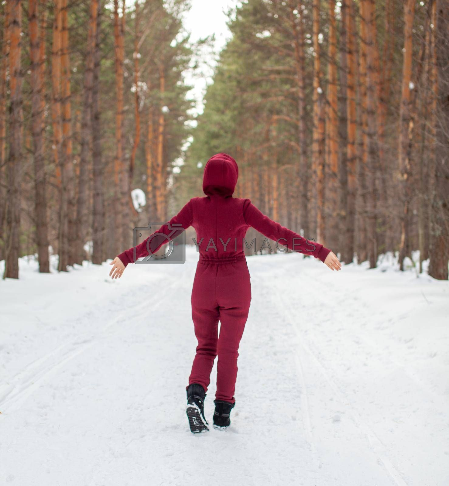 Winter walk in a snow-covered forest, A girl with a red jumpsuit and jacket walks among tall trees in nature. Solitude and relaxation from the hustle and bustle of the city.
