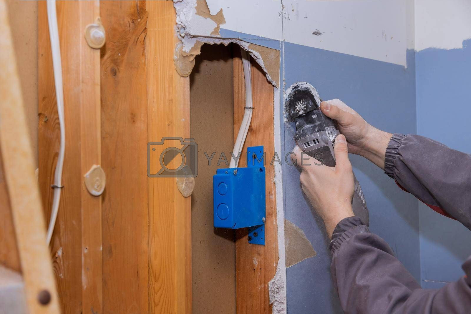 Home renovation service repair works of replacement damaged drywall on worker cutting plasterboard with construction electric power tools