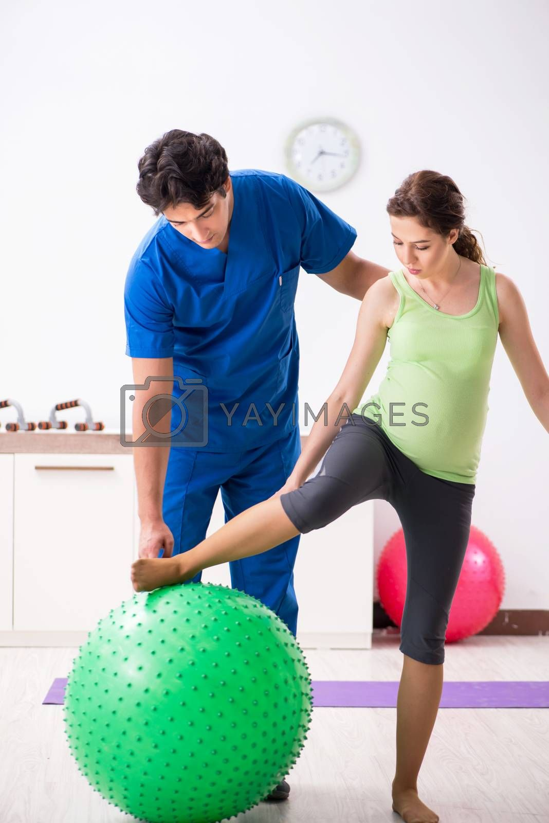 Fitness instructor helping sportsman during exercise