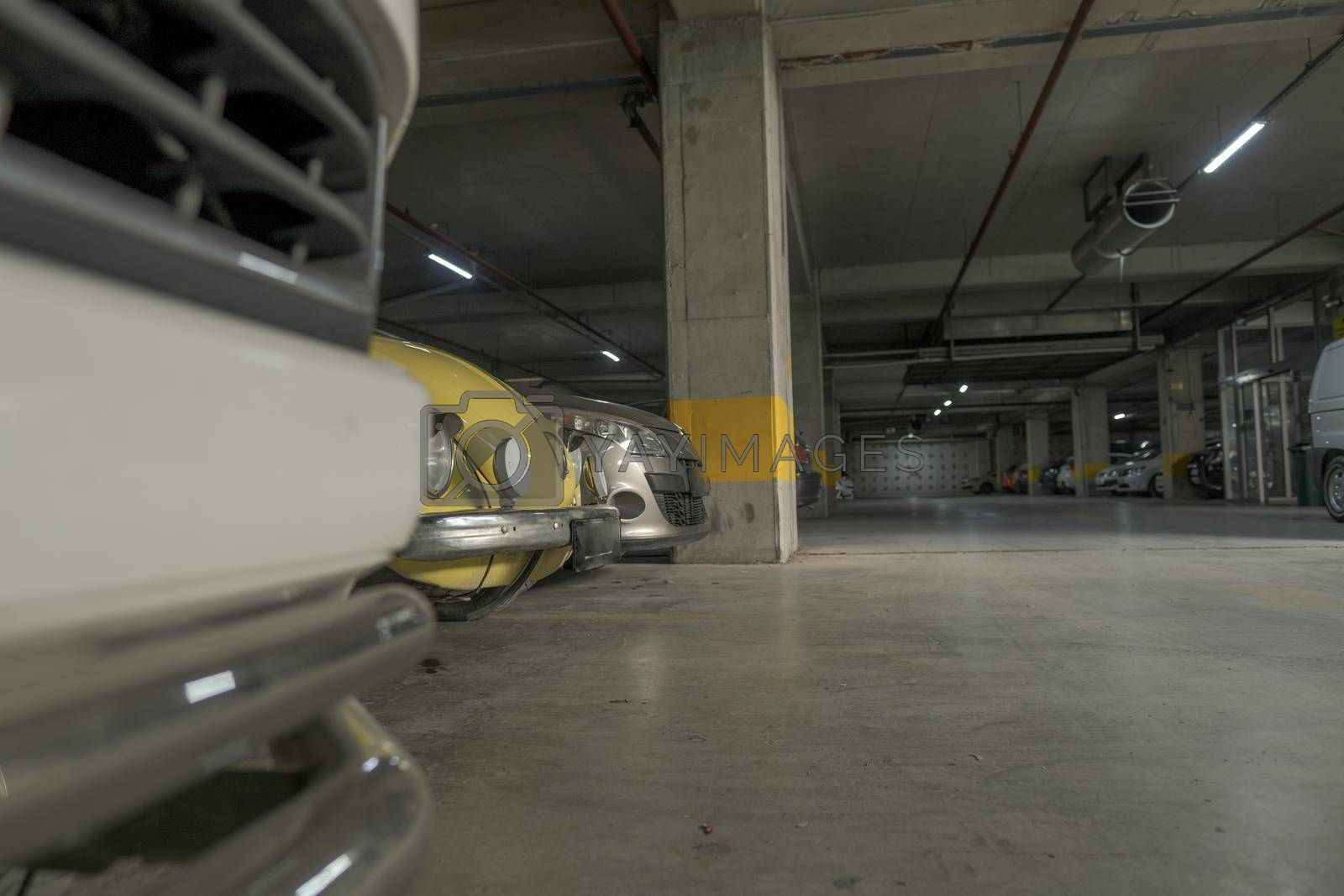 horizontal view of a car garage and some cars positioned in line