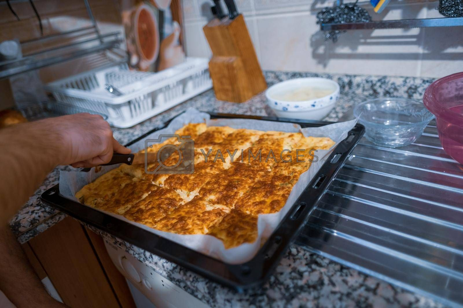 hands of a male person slicing borek in his kitchen