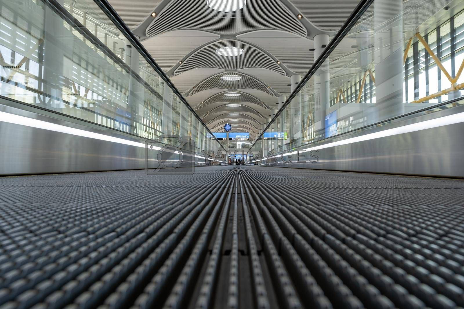 low angle of people mover in an airport with some unrecognizable people