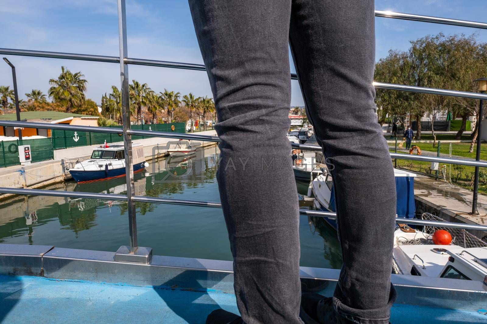 river and boats and a male person standing on a bridge in town in holiday time