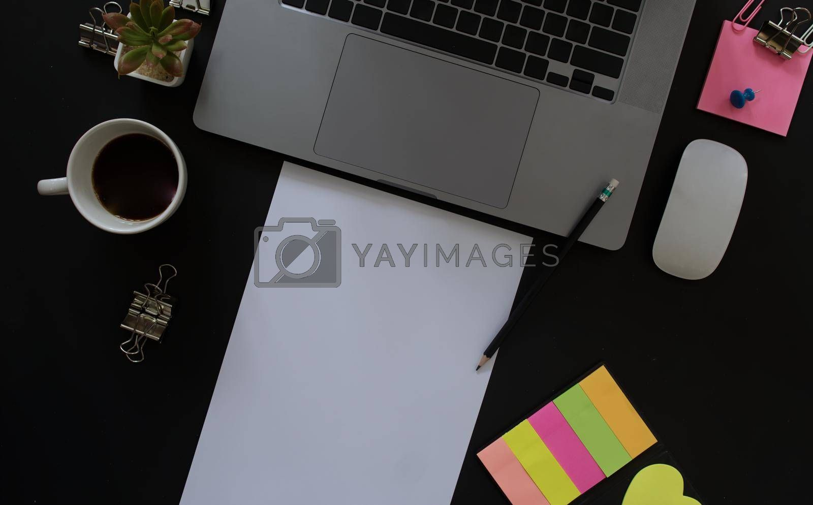 Business desk with laptop and memo paper placed on a black background, including a copy area to add text or graphics.