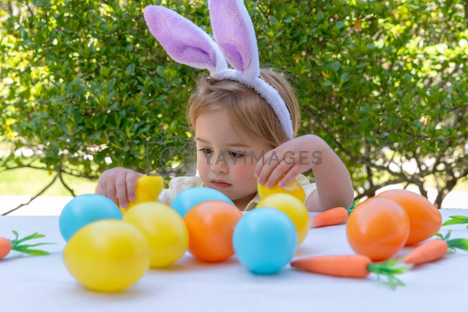 Little Baby Dressed as Bunny Playing with Colorful Eggs and Chick Toys. Traditional Easter Decorations. Spring Christian Holiday. Egg Hunt.