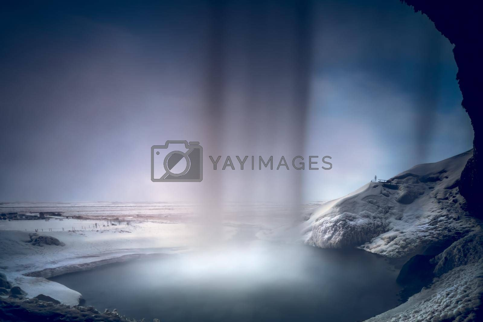 Beautiful View from inside of Seljalandsfoss Waterfall. Powerful Stream of the River. Amazing Winter Landscape. Famous Tourists Attraction of Iceland.